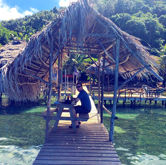 a traveller at an ocean bar on the island of Roatan, Honduras.